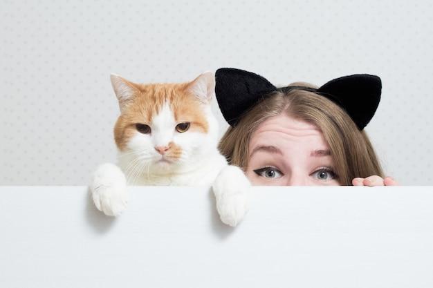 Jonge vrouw met kattenoren op haar hoofd en kat verstopt zich achter een witte banner. Premium Foto