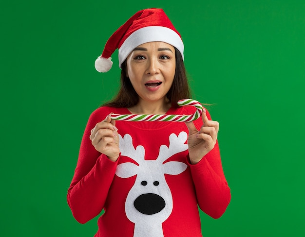 Jonge vrouw met kerst kerstmuts en rode trui bedrijf candy cane kijken camera blij en vrolijk permanent over groene achtergrond Gratis Foto