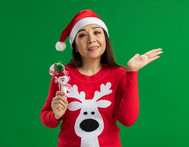 Jonge vrouw met kerst kerstmuts en rode trui bedrijf kerst candy cane kijken camera glimlachen met opgeheven arm staande over groene achtergrond Gratis Foto