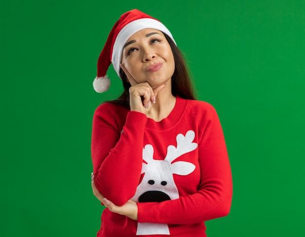 Jonge vrouw met kerst kerstmuts en rode trui opzoeken denken positief staande over groene achtergrond Gratis Foto