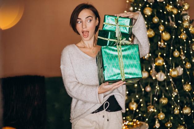 Jonge vrouw met kerstcadeau bij de kerstboom Gratis Foto