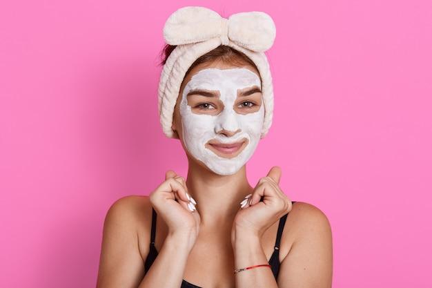 Jonge vrouw met kleimasker op haar gezicht het stellen tegen rooskleurige muur, vrolijk meisje die de zorg van de huidzorg thuis doen, in goede stemming zijn, die vuisten dichtbij gezicht houden. Premium Foto