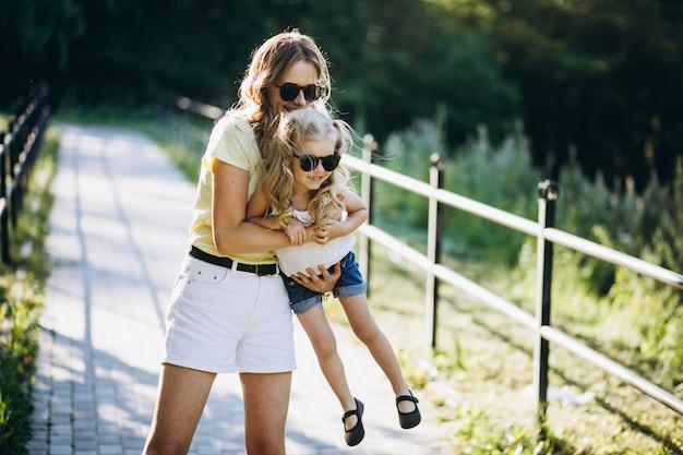 Jonge vrouw met kleine dochter die in park loopt Gratis Foto