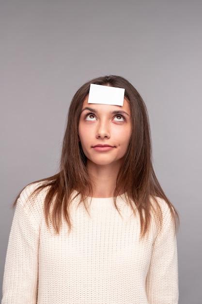 Jonge vrouw met kleverig document op voorhoofd Premium Foto