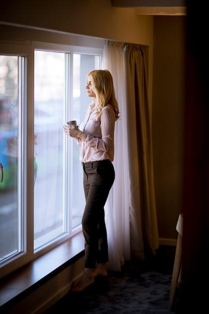 Jonge vrouw met kop thee of koffie die en het venster thuis bevinden zich drinken Premium Foto