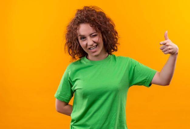 Jonge vrouw met kort krullend haar in groen t-shirt gelukkig en positief knipogend duimen opdagen die zich over oranje muur bevinden Gratis Foto
