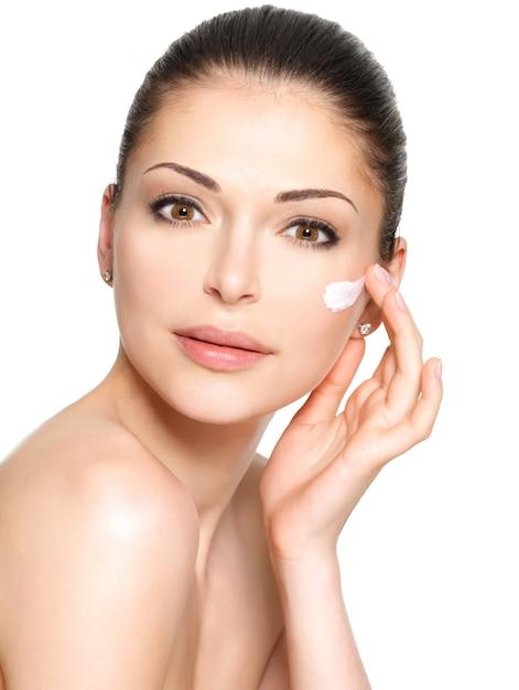 Jonge vrouw met kosmetische room op een schoon, fris gezicht. huid zorg concept Gratis Foto