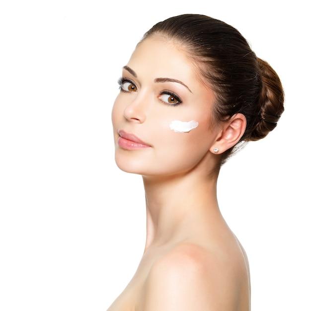 Jonge vrouw met kosmetische room op een schoon, fris gezicht Gratis Foto