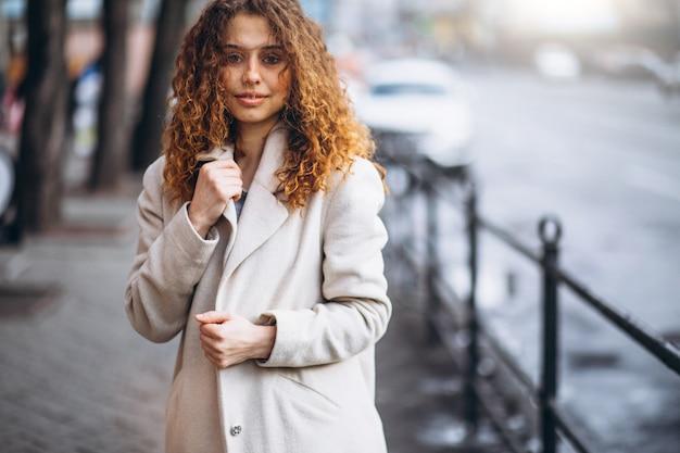 Jonge vrouw met krullend haar buiten de straat Gratis Foto
