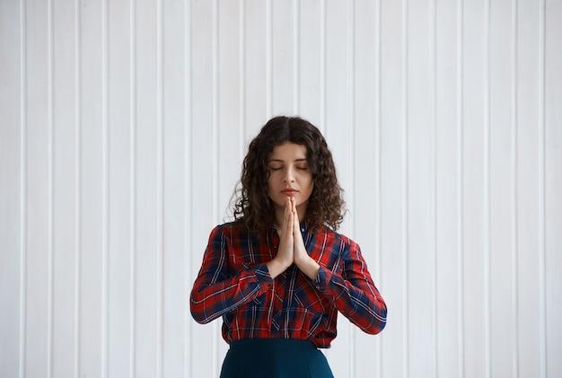 Jonge vrouw met krullend haar en geruit overhemd bidden Gratis Foto