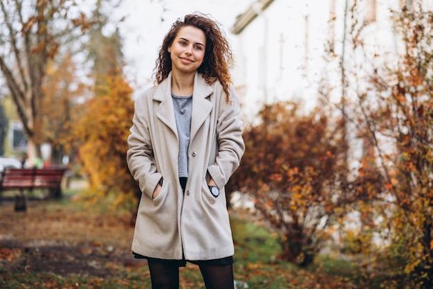 Jonge vrouw met krullend haar in park Gratis Foto
