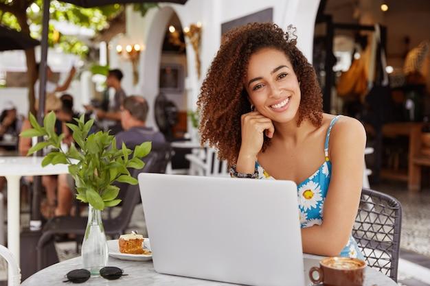 Jonge vrouw met krullend haar zittend in café met laptop Gratis Foto