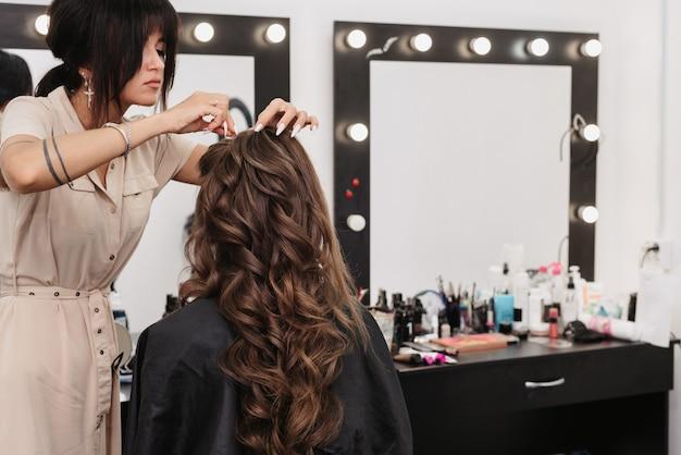 Jonge vrouw met lang bruin krullend haar in een schoonheidssalon Premium Foto