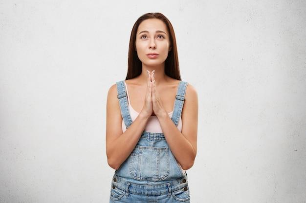 Jonge vrouw met lang donker steil haar opzoeken hopelijk bidden met haar handen gevouwen Gratis Foto
