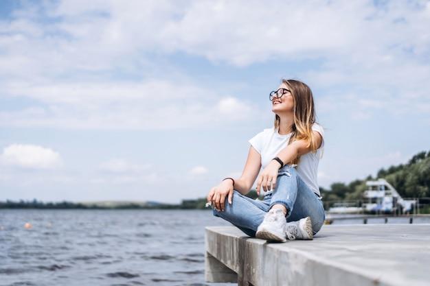 Jonge vrouw met lang haar in stijlvolle glazen poseren op de betonnen kust in de buurt van het meer. het meisje kleedde zich in jeans en t-shirt die weg glimlachen kijken Premium Foto