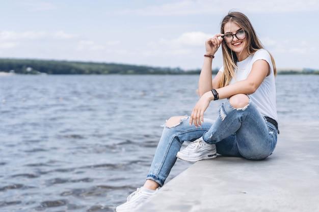 Jonge vrouw met lang haar in stijlvolle glazen poseren op de betonnen kust in de buurt van het meer. het meisje kleedde zich in jeans en t-shirt glimlachend en bekijkend de camera Premium Foto