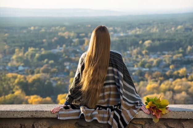 Jonge vrouw met lang haar zit op een heuvel met uitzicht op de stad. achteraanzicht Premium Foto
