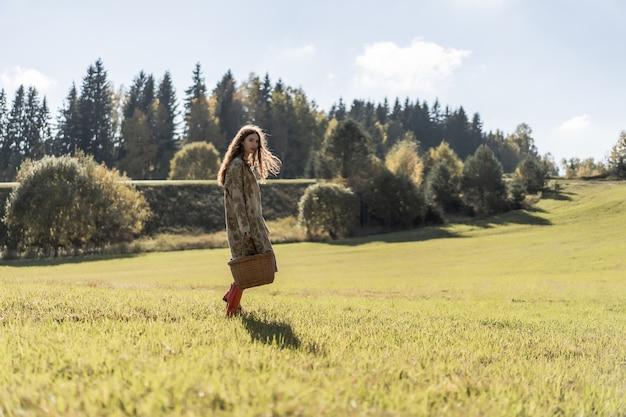 Jonge vrouw met lang rood haar in een linnenkleding die paddestoelen in het bos verzamelen Gratis Foto