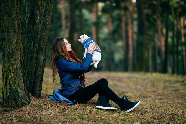 Jonge vrouw met lange zitting op grond voorbij bomen in bos met haar mooi chihuahuapuppy in handen. Premium Foto