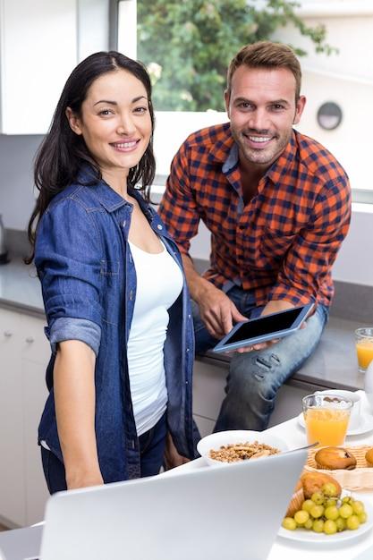 Jonge vrouw met laptop en man met behulp van digitale tablet Premium Foto