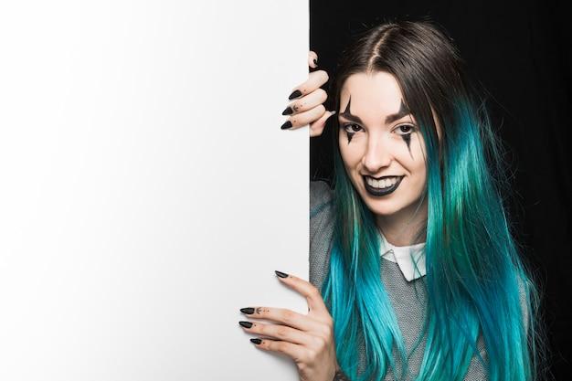 Jonge vrouw met make-up die achter achter witte raad te voorschijn komt Gratis Foto