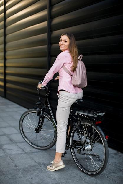 Jonge vrouw met moderne stads elektrische e-bike als schoon duurzaam stadsvervoer Premium Foto
