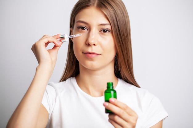 Jonge vrouw met mooie huid zet vitamines op haar gezicht Premium Foto