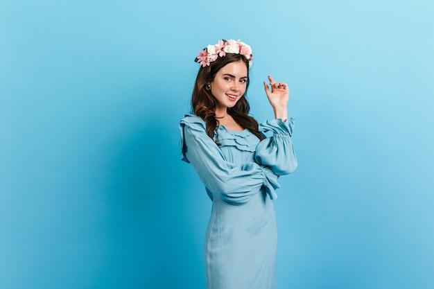 Jonge vrouw met naakt make-up en bloemen in haar haar. dame in hemelsblauw jurk poseren op geïsoleerde muur. Gratis Foto