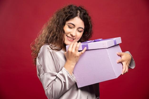 Jonge vrouw met paarse geschenkdoos. Gratis Foto