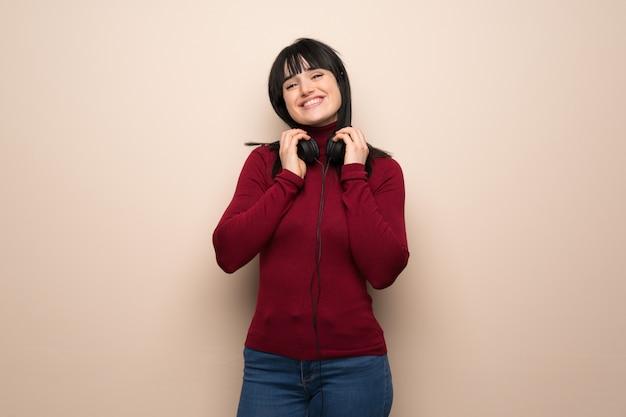 Jonge vrouw met rode coltrui met een koptelefoon Premium Foto
