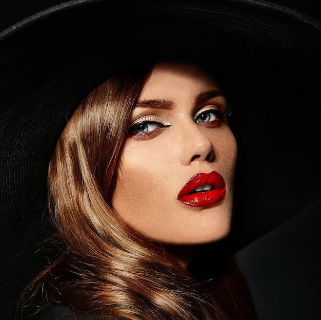 Jonge vrouw met rode lippen en zwarte hoed Gratis Foto