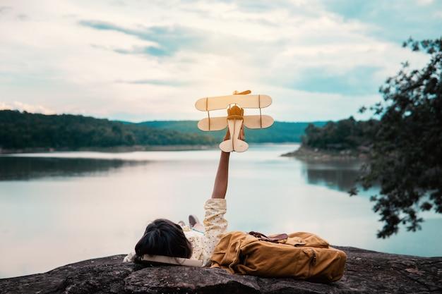 Jonge vrouw met rugzak en vliegtuigmodel door het meer Premium Foto
