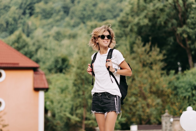 Jonge vrouw met rugzak reizen in de bergen met opgeheven handen en uitzicht op de vallei, reis, avonturen, weg, reiziger Gratis Foto