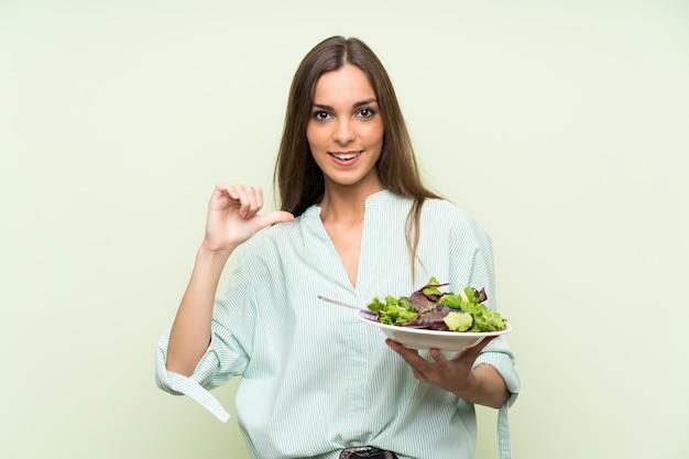 Jonge vrouw met salade over geïsoleerde groene trots en zelf-tevreden muur Premium Foto