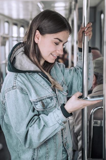 Jonge vrouw met telefoon in openbaar vervoer Gratis Foto