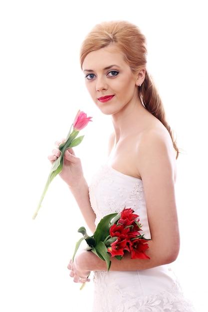 Jonge vrouw met trouwjurk en boeket Gratis Foto