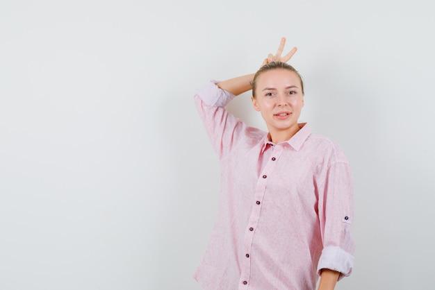 Jonge vrouw met v-teken achter het hoofd als hoorns in roze shirt en ziet er grappig uit Gratis Foto