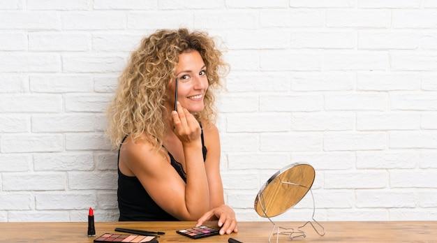 Jonge vrouw met veel make-upborstel in een lijst Premium Foto