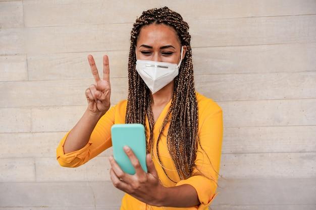 Jonge vrouw met vlechten die videogesprek doen terwijl het dragen van gezichts beschermend masker voor coronaviruspreventie Premium Foto