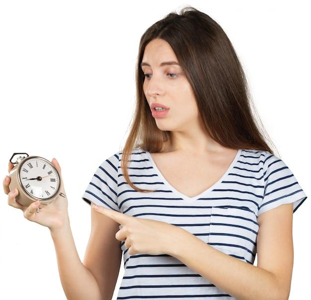 Jonge vrouw met wekker die op wit wordt geïsoleerd. tijd management concept Premium Foto