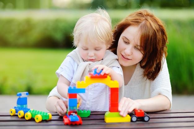 Jonge vrouw met zijn peuterzoon het spelen met kleurrijke plastic blokken Premium Foto