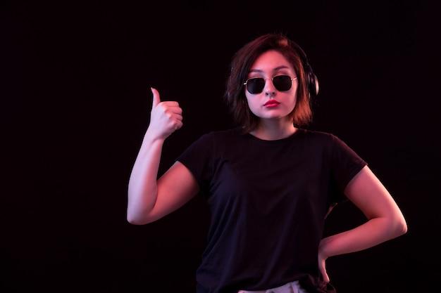 Jonge vrouw met zonnebril en zwart t-shirt met een koptelefoon Gratis Foto