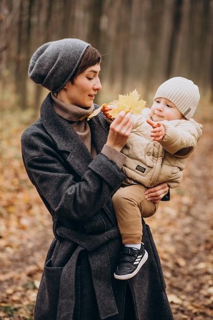 Jonge vrouw met zoontje wandelen in herfst park Gratis Foto