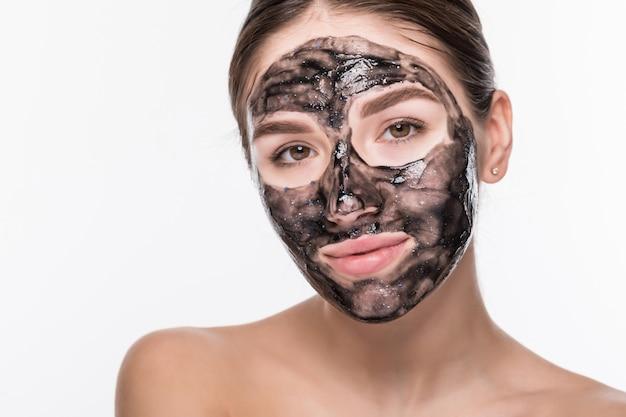 Jonge vrouw met zuiverend zwart masker op haar gezicht dat op witte muur wordt geïsoleerd Gratis Foto