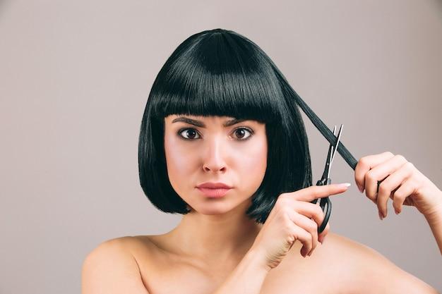 Jonge vrouw met zwarte haren poseren. ernstige zelfverzekerde brunette met bob-kapsel. schaar vasthouden en stuk haar knippen. Premium Foto