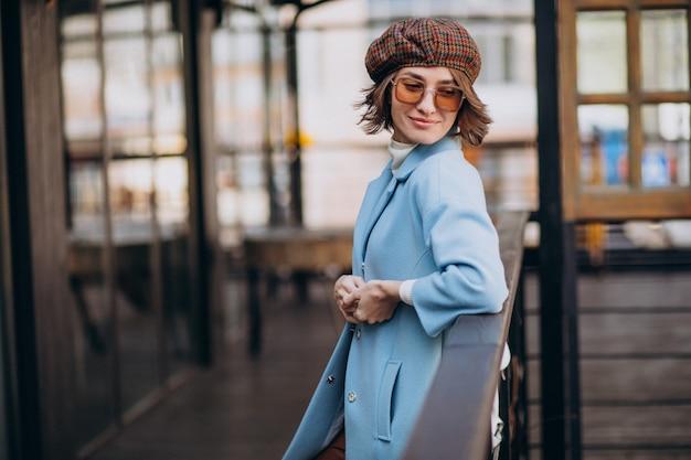 Jonge vrouw model in blauwe jas door het café Gratis Foto