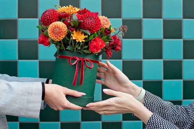 Jonge vrouw mooie pioenroos bloemen ontvangen levering vrouw. Premium Foto