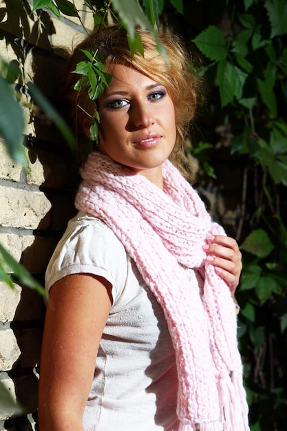 Jonge vrouw naast een bakstenen muur Gratis Foto