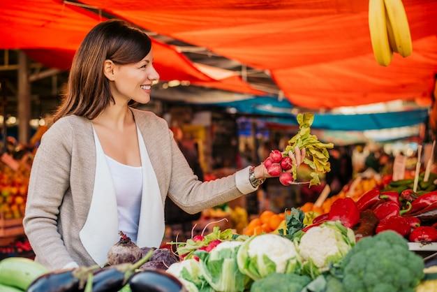 Jonge vrouw op de groene markt het kopen van groenten. Premium Foto