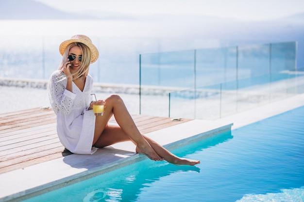 Jonge vrouw op een vakantie bij het zwembad met behulp van de telefoon Gratis Foto